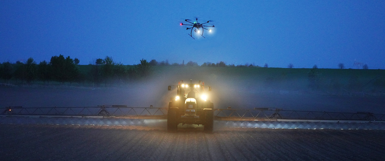 stock-photo-aerial-image-of-tractor-spraying-soil-and-young-crop-in-springtime-in-field-1074836360